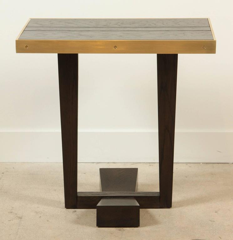 The Rialto Table is made from American walnut or white oak and features a satin brass banding and bow tie base. Shown here in Dark Greywashed Oak.  Made to order in various finishes with a 10-12 week lead time.
