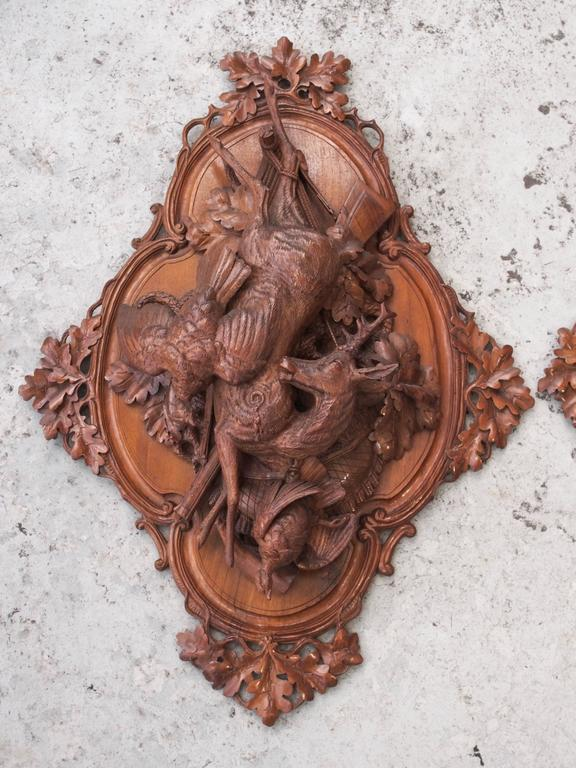 Pair of Black Forest carved wood wall plaques of game of the hunt.