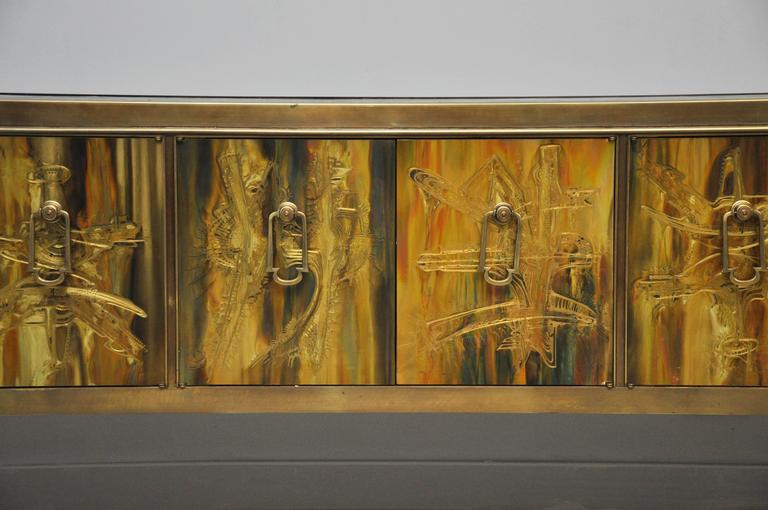 Brass credenza designed by Bernhard Rohne for Mastercraft. Brass panels were acid etched by Rohne to produce this magnificent piece of art. Doors open to a gold interior.