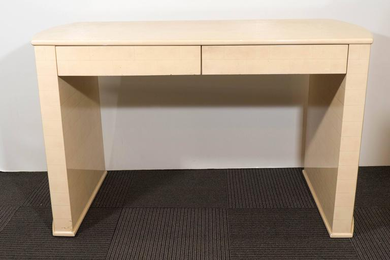 A vintage knee-hole desk, in the manner of designer Karl Springer, with slightly curved ends, in tessellated faux parchment with resin finish; includes two drawers with recessed pulls underneath. Overall good condition, with age appropriate wear,