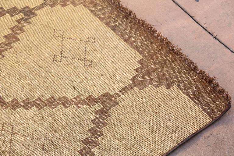 Moroccan Tuareg leather mats are made of dwarf palm tree fibers and hand-woven with leather stripes, this are great to use indoor or outdoor, beautiful brown earth-tone colors. This vintage mid century carpets are made in the desert of Morocco near