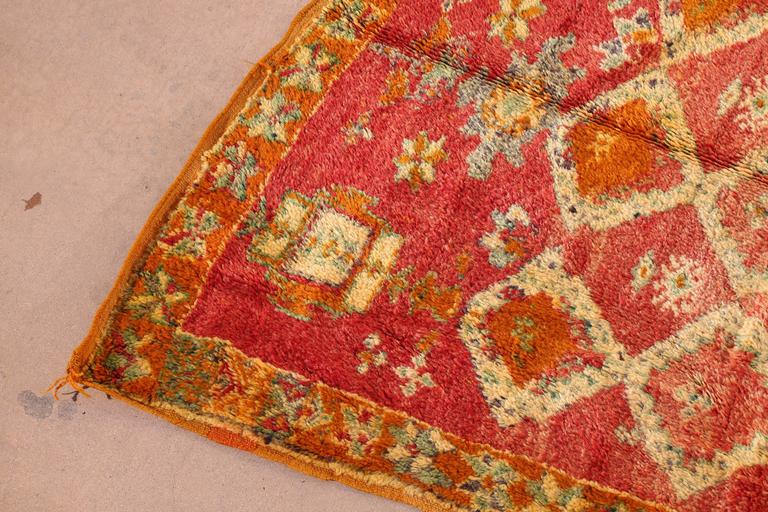 Great happy colors in this vintage Moroccan tribal rug, hand woven by women in Morocco. Orange with pink, yellow, cream and turquoise colors in lozenges and geometric designs.