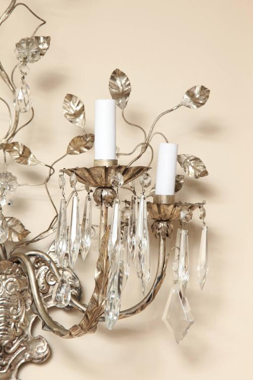 A pair of 4-light silver metal wall sconces with vase-shaped backplates having shield motif, issuing four candle arms having leaf-shaped ornaments and bobeches draped with crystal drops, the backplate issuing up-swept branches with leaves and