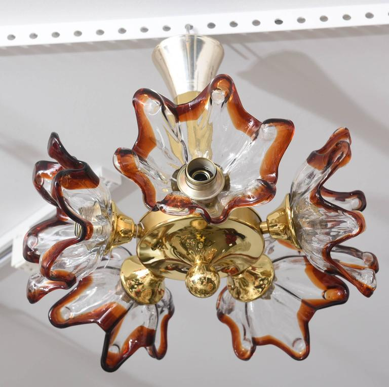 "This amazing Mid-Century chandelier with its five Murano glass stylized floral blossoms in clear and amber-colors was created by the iconic firm Mazzega in the 1960s. The blossoms approximately measures 7"" diameter x 7"" depth.