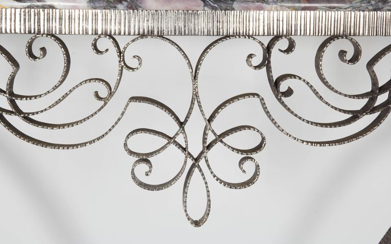 An original French Art Deco hand-forged, satin nickeled iron console table attributed to Poillerat. This exquisite console features an elegant shaped base ending with tear drop finial, topped by a lyrical scroll curvilinear apron supporting its