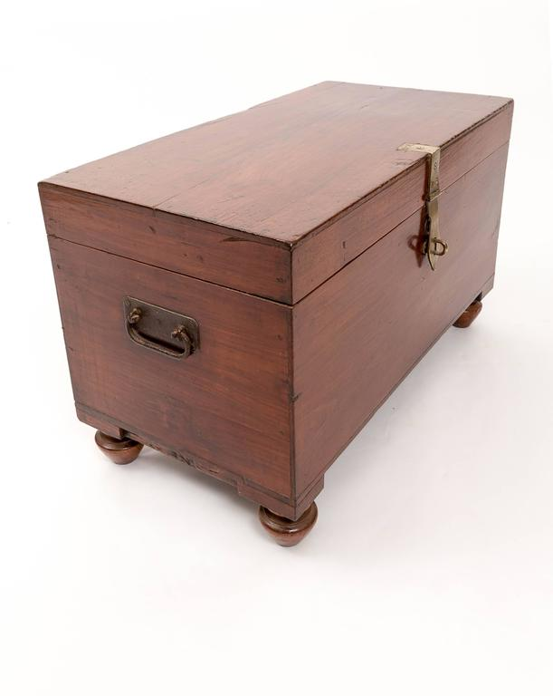 Teak trunk on bun feet with iron carrying handles and brass clasp.