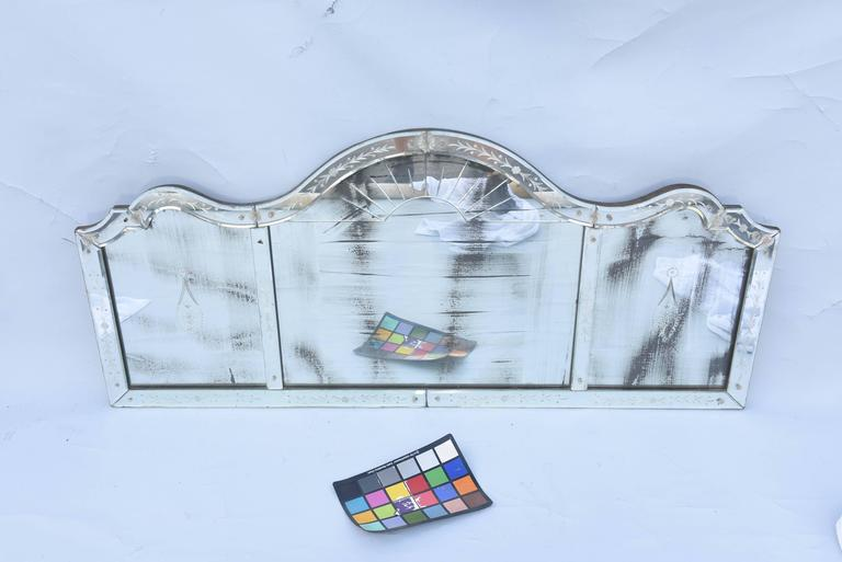 Tripartite overmantel mirror, each panel with natural wear to silvering, its serpentine pediment decorated with foliate decoration, adorned with glass rosettes, each panel with decorative etching.  Stock ID: D8253