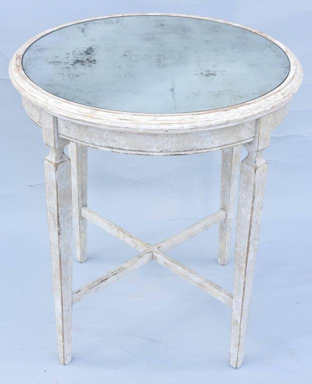 Swedish style occasional, or end table, having a round top of distressed mirror, inset on painted table base, showing natural wear, its fielded apron, raised on four, square-section, tapering legs, joined by X-stretcher. 