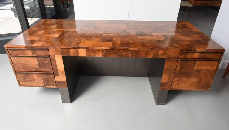 The body overall with burled walnut patchwork, with two drawer compartments flanked by two central pencil drawers the legs and base all in pewter patchwork, signed Paul Evans, 1972.