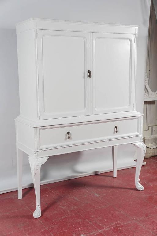 Freshly painted white, the early 20th century china cabinet has one generous size dovetail drawer and two shelves behind a pair of paneled doors. One shelf has slots for angling plates.