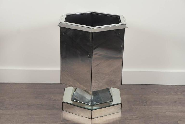 Six sided, hexagon footed planter, in handsome mitered and beveled mirror. With black metal removable liner. Several chips in the mirror, consistent with age and use.