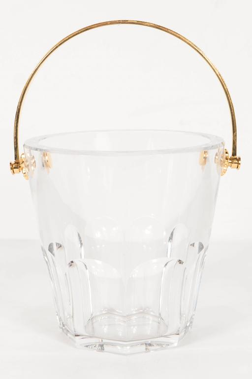 Ultra-luxe crystal ice pail with 24-karat gilt handle by Baccarat. Needed and stylized floral detailing and gold-plated fittings support an ornamented handle. An octagonal base and round, bevelled top give the crystal pail an elegant solidity.