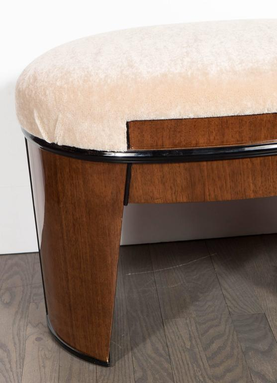This exceptional Art Deco skyscraper style stool features a streamlined ovoid design with a tapered cut-out style leg in bookmatched walnut with a black lacquer trim and new camel mohair upholstery. Restored to mint condition.
