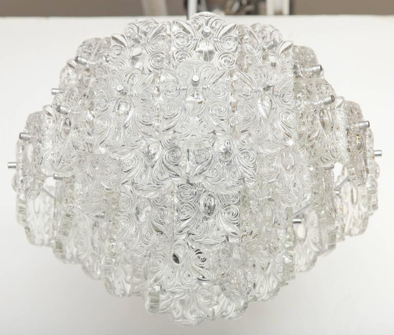 Striking Mid-Century chandelier composed of five tiers of crystal elements with a scroll design. Chandelier suspended from a nickel canopy and rod. Currently two are available. Rewired for use in the USA.