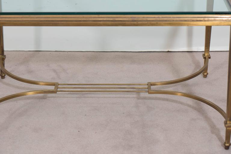 A vintage coffee table designed in the neoclassical taste circa 1950s, with glass top on a beveled brass frame and tapered legs, with harp form stretcher. This piece is in good condition, with age appropriate wear to finish, as well as minor