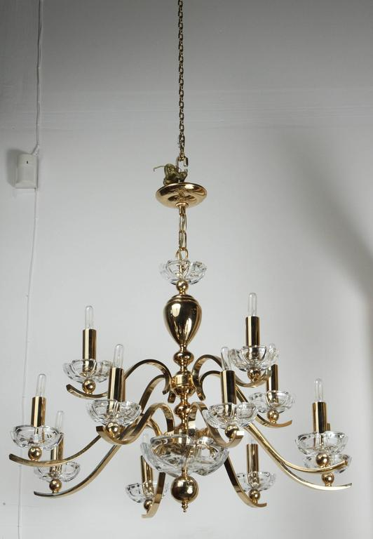 Elegant twelve-arm polished brass chandelier with glass bobeches. The chandelier is accompanied with matching ceiling canopy.