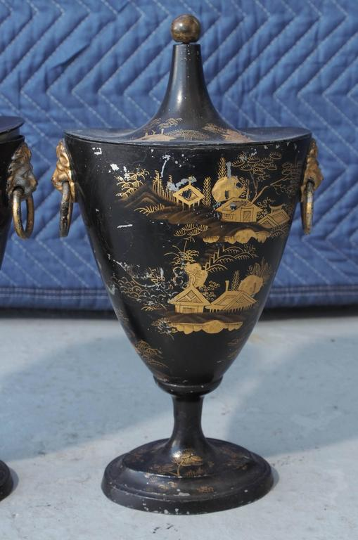 Pair of early 19th century tole chestnut urns with chinoiserie decoration with conical lids in ovoid form. Ringed gilt lions head handles and ball finials.