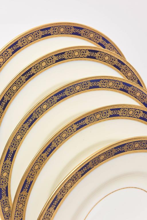 A set of 12 dinner plates by one of our favorite makers, Minton England. Custom ordered and made for Tiffany. These 12 plates feature 2 crisp 24k acid etched gilt bands with a nice design of raised tooled gold in a cobalt blue band on its collar. An