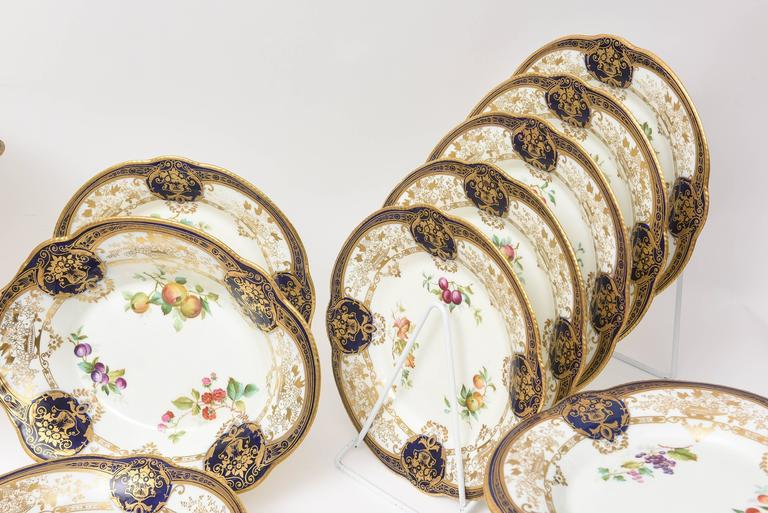 An elaborate and wonderful dessert service by a storied English porcelain firm: Adderly. Rich cobalt blue edges and cartouches, hand decorated 24-karat gilt throughout and hand-painted florals and fruits make this service especially beautiful.