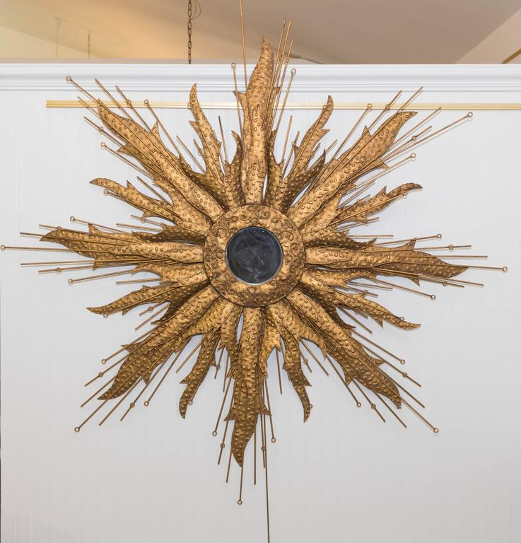 Metal sunburst shape mirror in the Brutalist style, radiating strips of metal forming sunrays with texture and iron rods interspersed throughout.