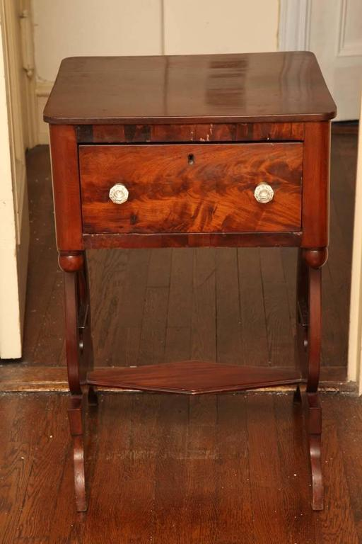 The rectangular top with rounded corners over a deep frieze drawer with lively flame figure and cut-glass knobs, raised on lyre-form end supports on downward swept feet.