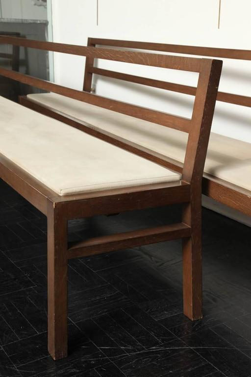 Pair of 20th century stained oak long benches, open-back, upholstered seats, straight square legs.