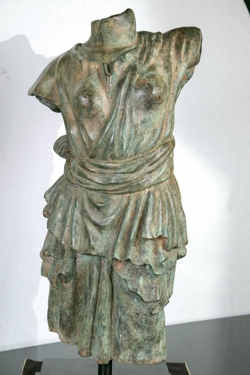Set upon a two stepped black base. The bronze having a green/brown patina. The torso wearing a sashed at the waist garment.  Measurements refer to the base.