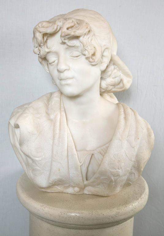 Her hair covered by a cap. She wears a collared covering decorated in low relief with flowers and leaves. Her undergarment visible and tied in a knot. Her eyes are partially closed.