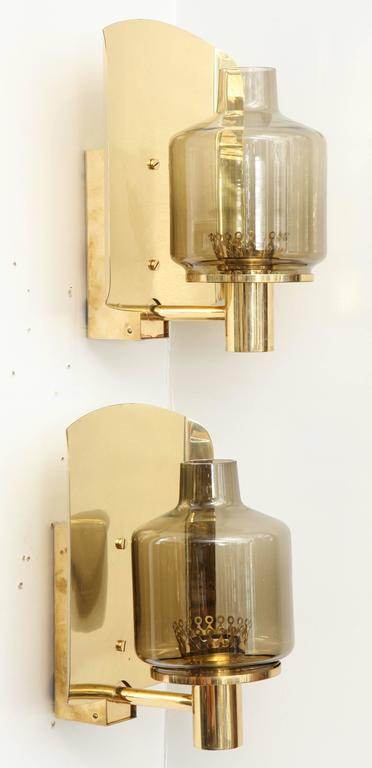 Pair of large-scale sconces composed of smoked glass globes on brass supports. Rewired for use in the USA.