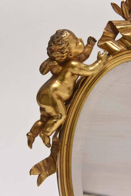 Very sweet Dore bronze vanity mirror adorned with garlands and putti on a Carnelian marble base.