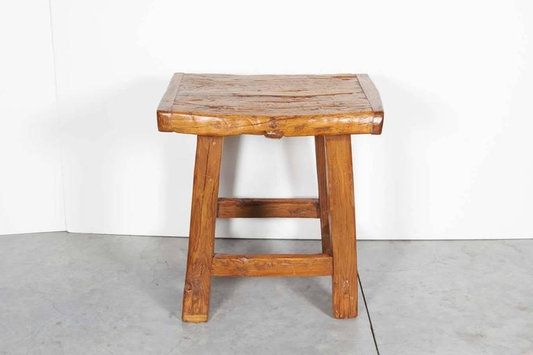A large antique Chinese stool with a solid two inch thick seat, easily usable as a side table. Great patina. From Shanxi Province, circa 1900.