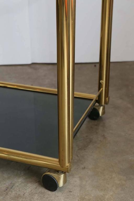 Offered is a Mid-Century Modern Art Deco inspired two-tier brass and glass bar cart signed by Design Institute America, with clear glass top shelf and smoked glass bottom shelf on brass wheels. Hollywood glam at its finest!