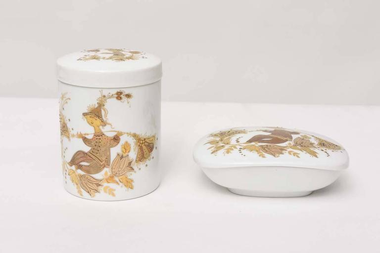 Romance pattern porcelain lidded canister and box by Bjorn Wiinblad with with 24-karat gold decoration on front, back, and lid of canister, and interior and lid of box. Box measures 2.25in. H x 5.75in. L x 4.5in. W. Canister measures 5in. height x