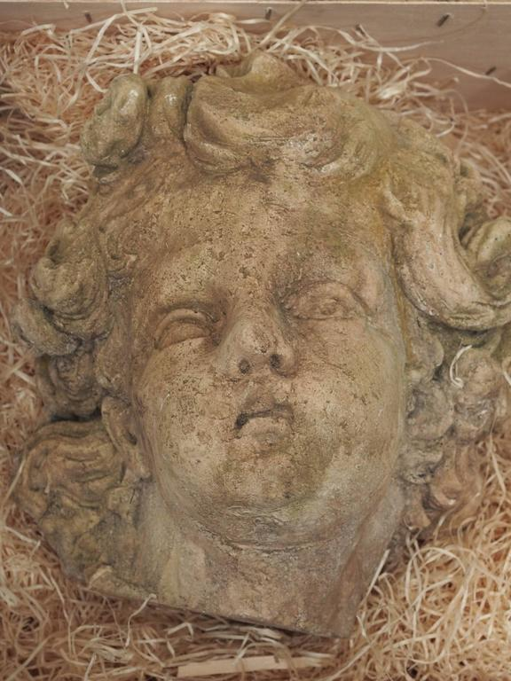 A plaster sculpted head of a cherub created during the late 19th century.
