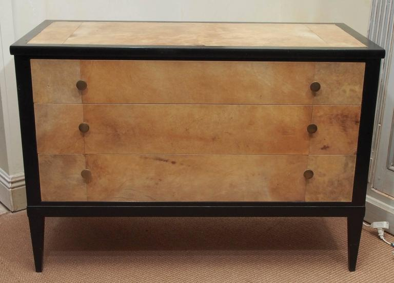 1950s Penquay commode with parchment panels on the top and the front of the three drawers. Drawers finished with brass flat-topped knobs.