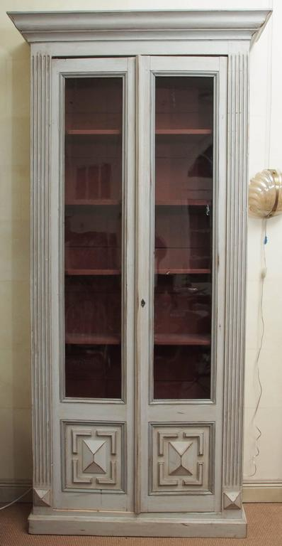 A pair of painted 18th century Louis XVI bookcases with glass panels and five shelves. Crown molding capitals and fluted molding running the length of each vertical edge. The bottoms of the doors are finished with carving and additional detailing.