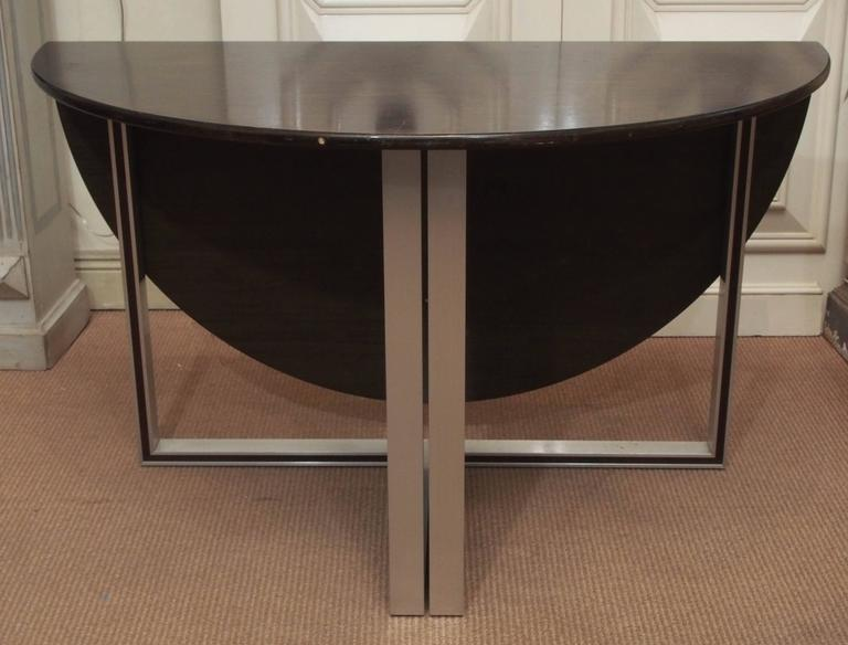 A beautiful modern circular table with a folding leaf and metal legs. The table can be flush with a wall or set as a standalone piece. Its versatility would make it a great addition to any space.