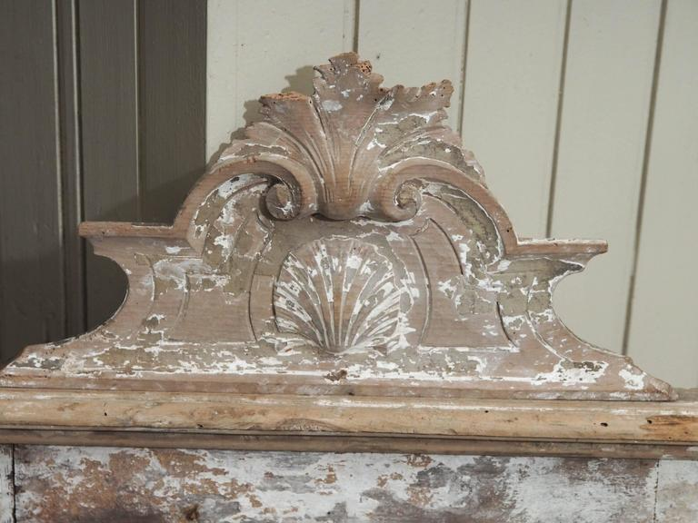 An original mercury glass mirror set into a painted wood frame featuring scroll work and leaf motifs. This piece would be lovely on a mantel (fireplace) piece or a shelf in an elegant space.