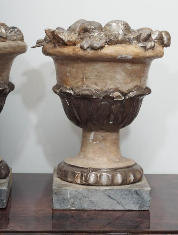 Two carved and silvered Bacchanalian wooden bowls of fruit on wooden pedestals.