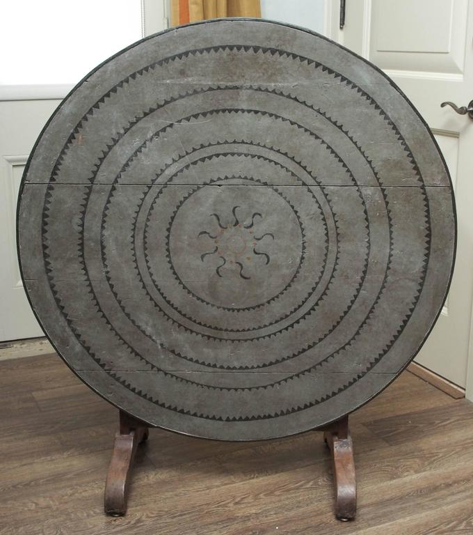 Turn of the century French oak wine table with painted canvas cover. The cover features a sun and radiating patterning. The table folds for storage.