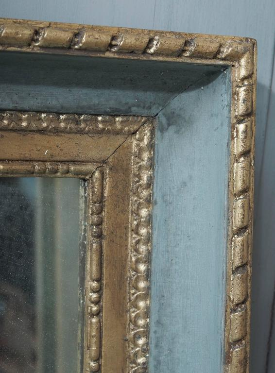 Framed pair of gilded and painted Louis XVI mirrors. Measures: 23 1/2 W x 31 H.