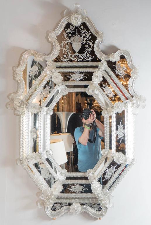 This exquisite Mid-Century Murano Venetian mirror features a crest form with scroll and reverse etched detailing throughout the borders. The mirror consists of a series of sections separated by rows of glass rods with a twist design and floral and