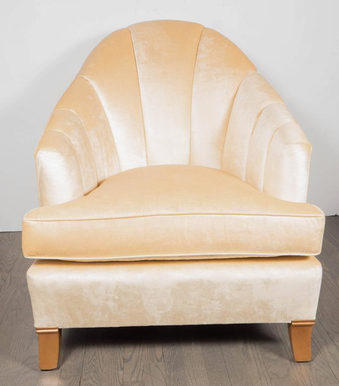 An elegant pair of French Art Deco club chairs with channel-back detailing. Newly upholstered in a cream oyster velvet fabric. Two rear-splayed and two front slightly-tapered walnut feet support each piece. A curved back and sloping arms make for a