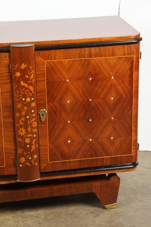 In the style of Andre Leleu the sideboard is done in a rosewood marquetry and inlaid with mother-of-pearl.