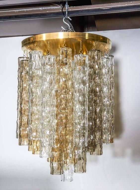 Mid-century modern chandelier comprised of three tiers of handblown Murano glass pendants with bamboo texture and design. The glass pendants come in alternating colors (smoked grey, amber, and clear). Features a large brass dome ceiling plate with