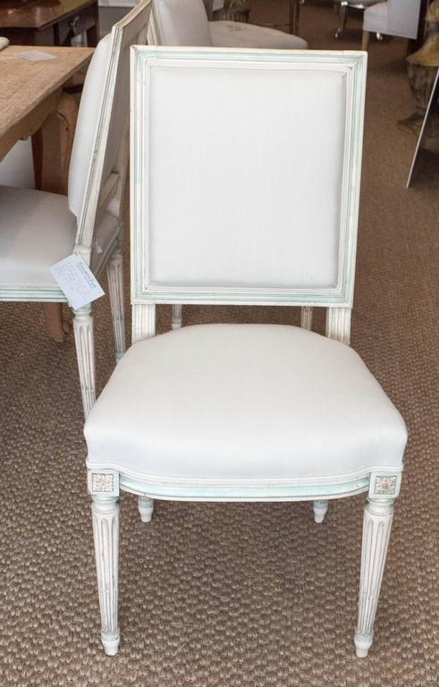 Timeless and elegant, these Louis XVI style chairs could feel at home in either contemporary or traditional surroundings. The back of the chair is squared, whereas the set is slightly curved, creating a gracious line. Painted in a grayish white,