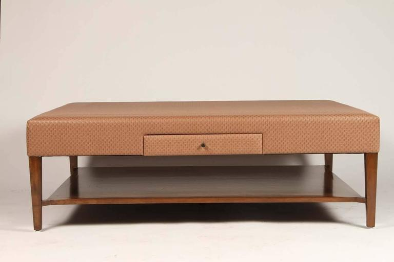 This large custom alder coffee table is upholstered in faux leather, with four drawers. Practical and versatile, this table will work in a variety of styles from traditional to contemporary.