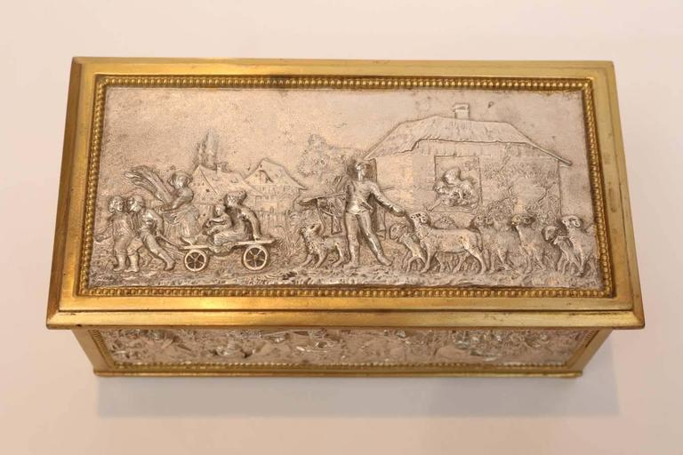 European silver and bronze dore box that is decorated with an attractive village scene. The interior is lined in red velvet.