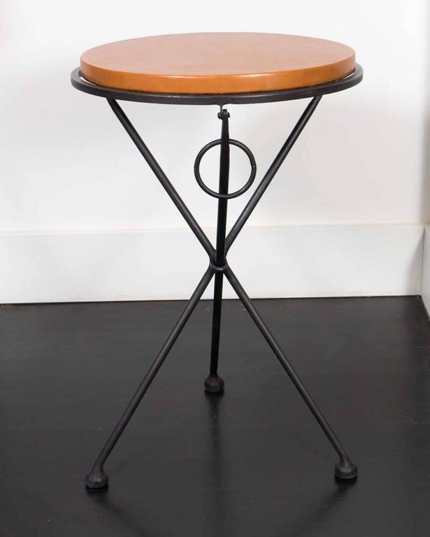 Pair of occasional tables from France. Hand-forged iron base with leather covered oak tops. Once lifted by the rings, these tables fold flat.