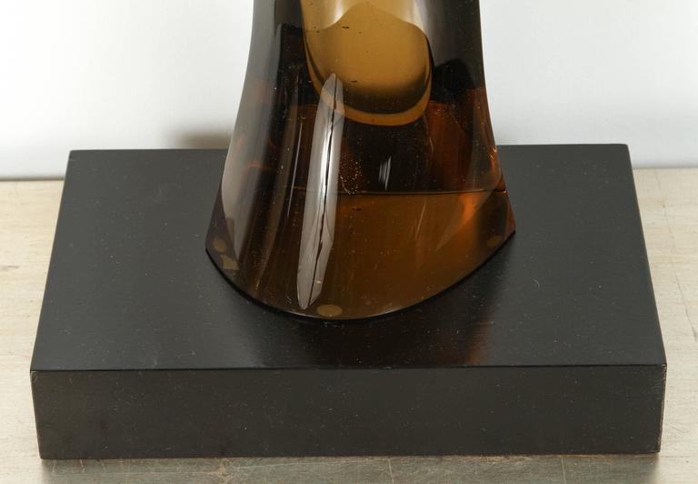 Sleek 1970s smoked glass sculpture set on a black wooden base.  The smooth glass undulates and tapers up from the base. It fades from a dark amber to nearly clear at the top.